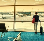 Businesswoman relaxing at airport lounge. Travel tourist woman standing with luggage watching sunset at window looking at airplanes waiting at boarding gate before departure. Travel lifestyle.